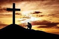 cross on hill, man kneeling